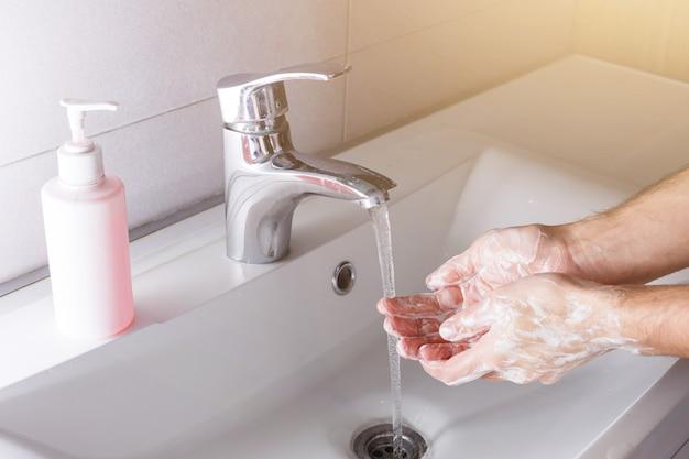 Man washes his hands near the white washbasin