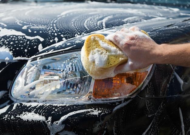 Мужчина моет мыльную машину желтой губкой.