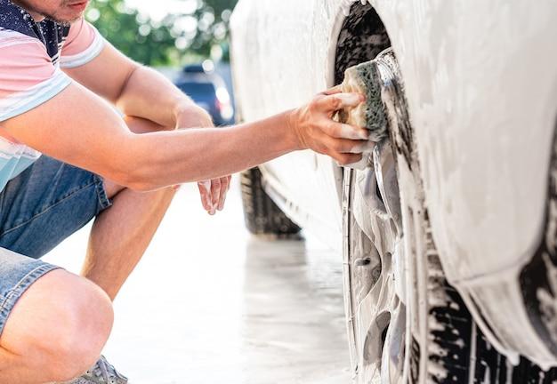 Человек моет колесо автомобиля губкой и пеной