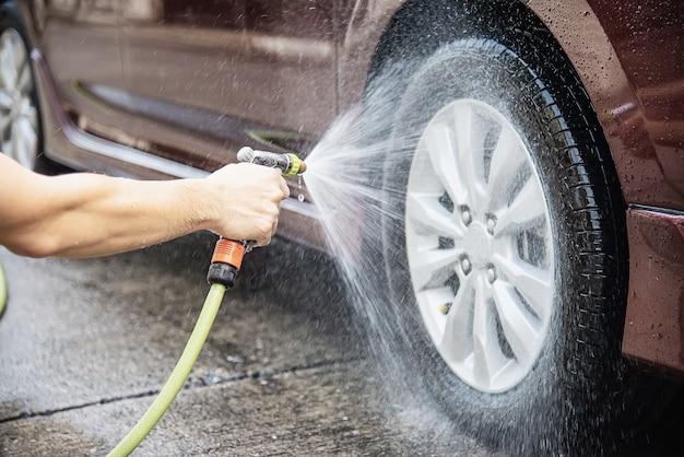 Человек моет машину, используя шампунь и воду