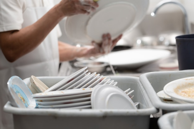 Мужчина моет посуду на раковине в ресторане