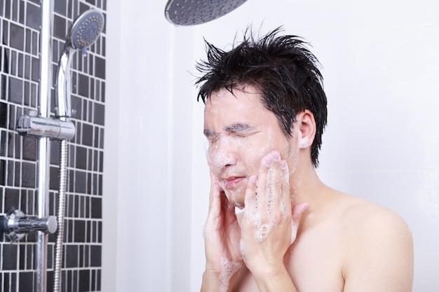 浴室で顔を洗う男