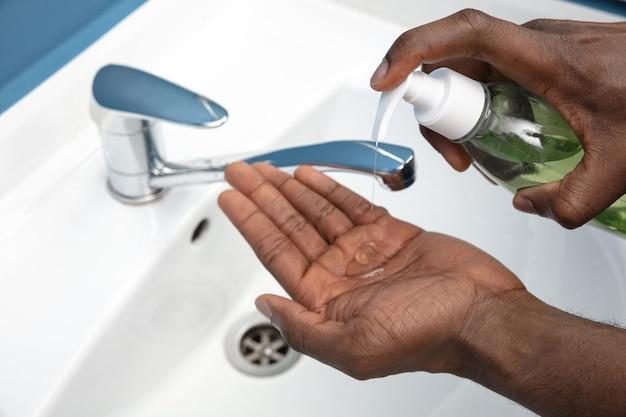 화장실에서 조심스럽게 손을 씻는 사람은 감염 예방을 닫습니다.