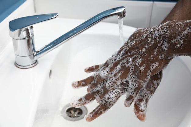 Uomo che si lava accuratamente le mani con sapone e disinfettante, primo piano. prevenzione della diffusione del virus della polmonite, protezione contro la pandemia di coronavirus. igiene, sanitario, pulizia, disinfezione. sicurezza.