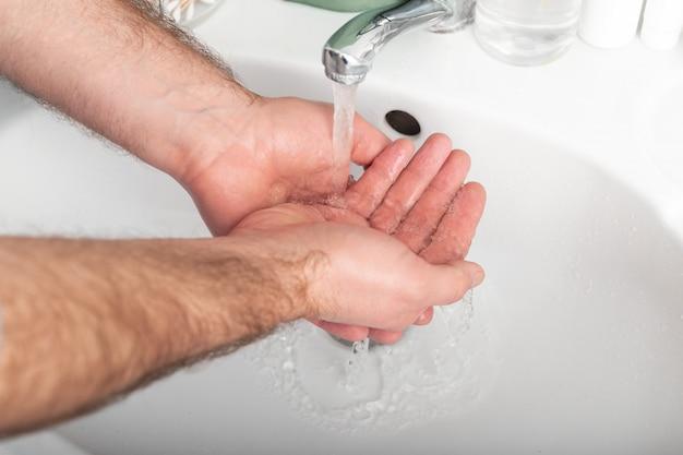 抗菌石鹸と水で手を洗う人。コロナウイルス保護手指衛生。 covid-19に対するヘルスケアのための皮膚消毒剤