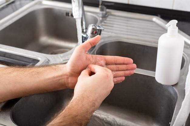 コロナウイルス予防のために抗菌石鹸と金属シンクの水で手を洗う人。手指衛生、ヘルスケア、医療の概念。手の皮膚の消毒はコロナウイルスのcovid19から保護します。