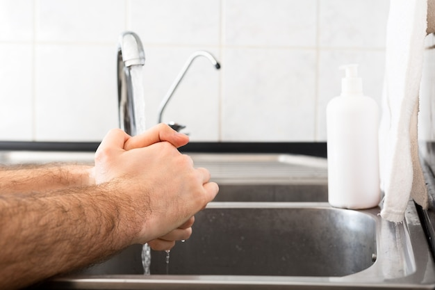 Man washing hands with antibacterial soap and water in metal sink for corona virus prevention. hand hygiene, health care, medical concept. hand skin disinfection protect from coronavirus covid 19.