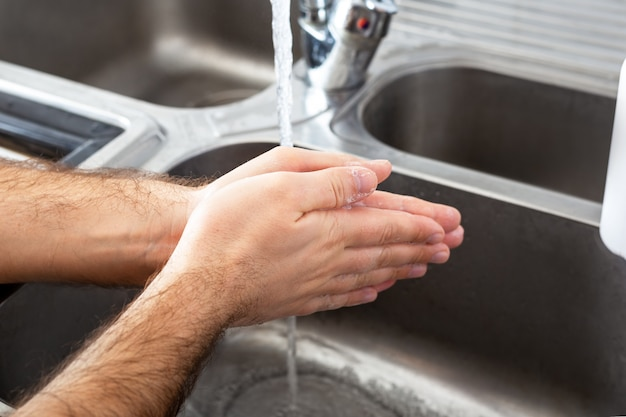 Man washing hands with antibacterial soap and water in metal sink for corona virus prevention.
