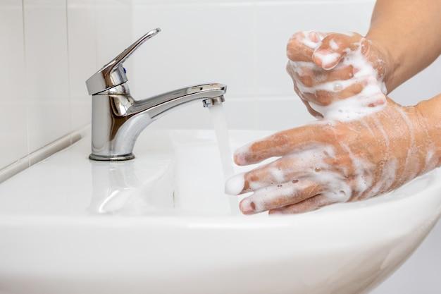 コロナウイルスの予防のために手を洗う人。
