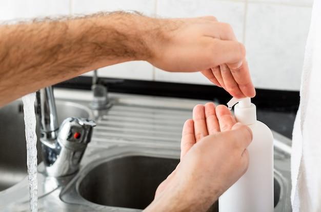 コロナウイルス予防のために金属シンクで石鹸と水で手を洗う人。手指衛生