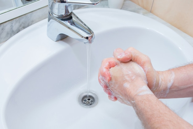Man washing hands with soap under bathroom sink.