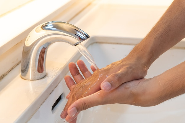 Man washing hands with soap under the faucet with water  in the bathroom.