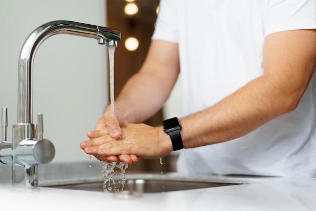 自宅の流しで石鹸で手を洗う男がクローズアップ