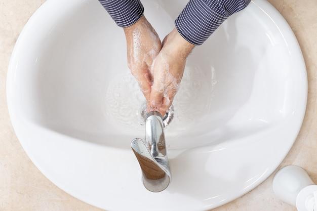 Человек, мытье рук с водой и мылом на ванной. концепция профилактики коронавирус