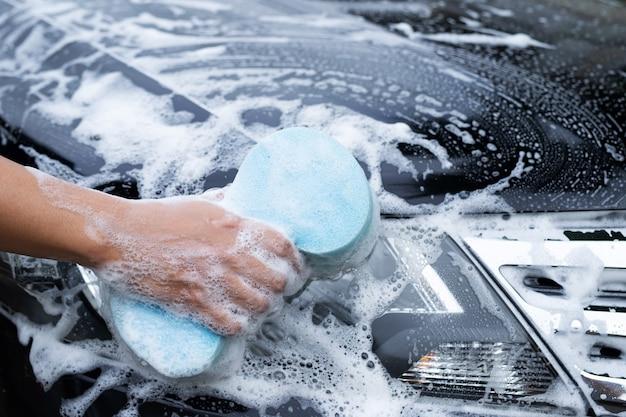 먼지를 청소하기 위해 파란색 스폰지로 그의 검은 차를 세척하는 남자.