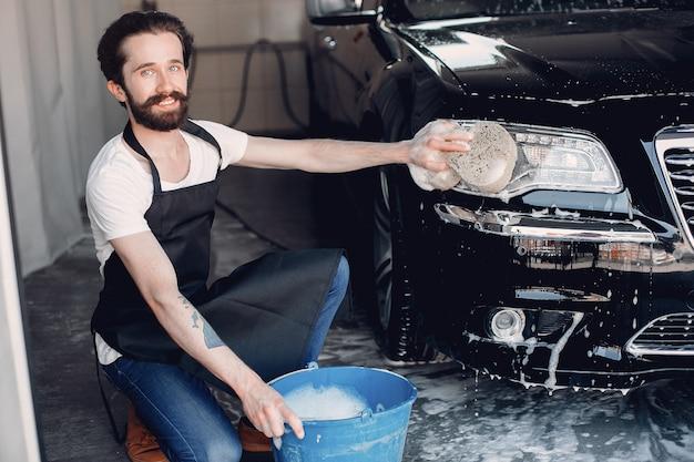Man washing his car in a garage