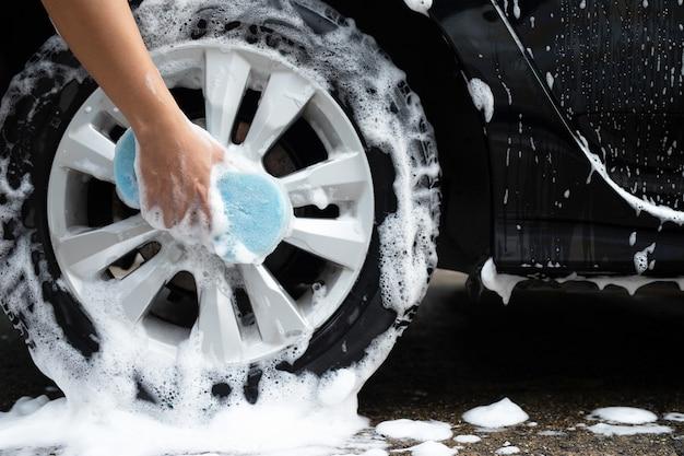 Мужчина моет колеса своей машины, чтобы удалить грязь с помощью синей губки.