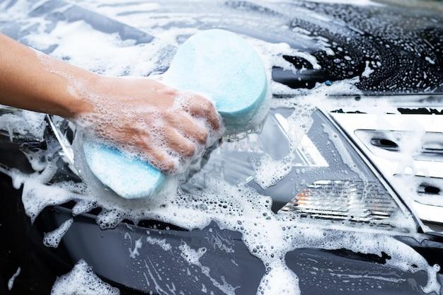 차를 청소하기 위해 그의 차를 세척하는 남자