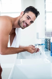 Man washing his face in sink in bathroom