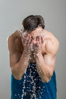 Man washing his face with water