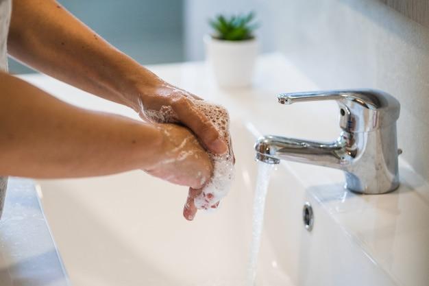 トイレの流しで手を洗う人
