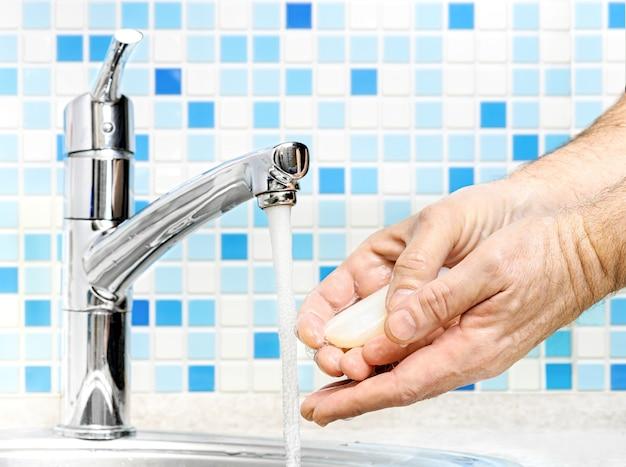 흐르는 물에 비누로 손을 씻는 남자