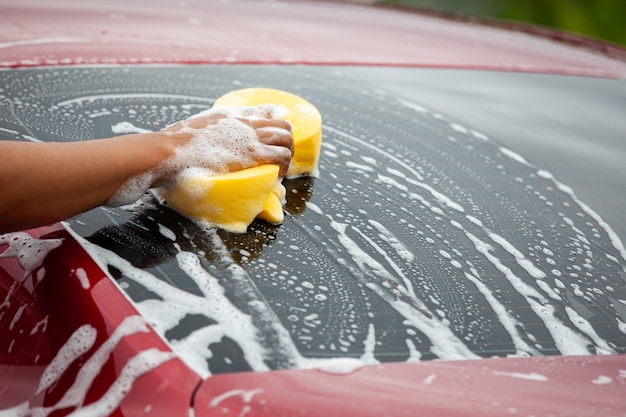Человек, моющий красный автомобиль с губкой и мылом