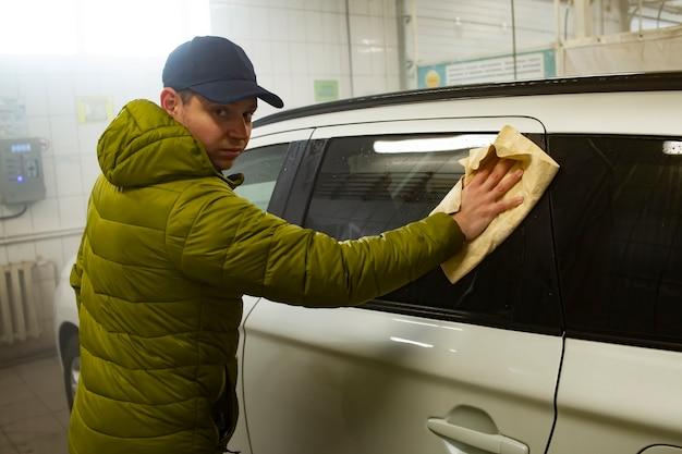 ボディワークをシャンプーした後、専用のクリーニンググローブで車の表面を拭いて洗車する男