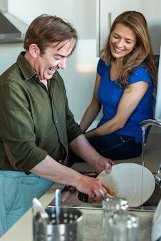Мужчина моет посуду со своей женой рядом с ним. фото высокого качества