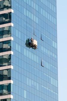 고층 건물에 창문을 씻는 남자