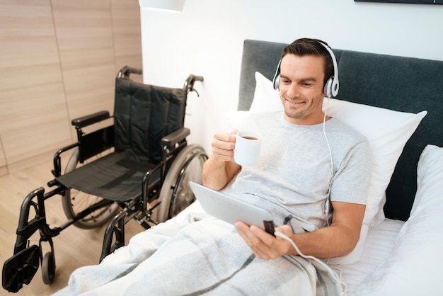 Man watch video in pad in headphones and hold cup.