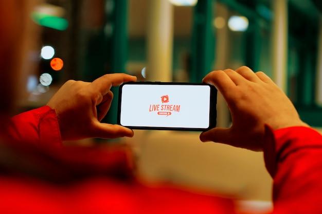 男はスマートフォンの画面で生放送を見ています。携帯電話の画面にあるボタンライブストリーム。
