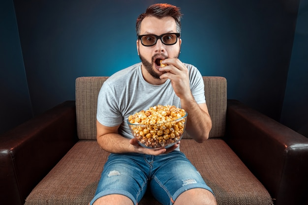 A man watches a movie or series with 3d glasses, a blue wall. the concept of a cinema, films, emotions, surprise, leisure, streaming platforms.