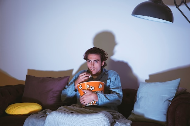 映画を見てポップコーンを食べる男