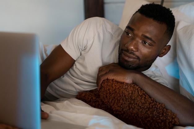 自宅でnetflixで映画を見ている男