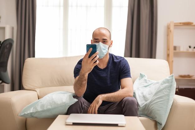 검역 중 소파에 앉아 보호복을 입고 스마트폰으로 비디오를 보는 남자.