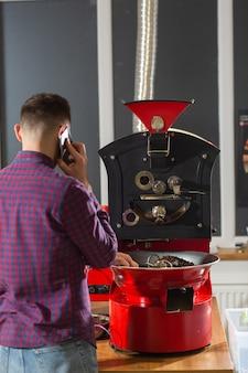 곡물 냉각기가 있는 현대적인 장비에 있는 romatic 커피 콩을 보고 있는 남자. 산업 개념입니다. 콩을 굽는 데 사용되는 현대적인 기계. 냉각 실린더에 커피 로스터를 붓고 있습니다.