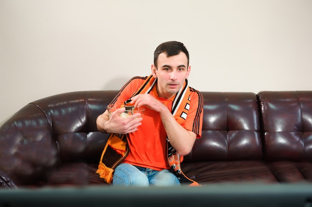 Man watching football, football fan, sports at home.
