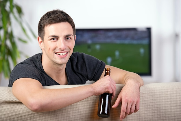 Man watching a football game on sofa with a beer.