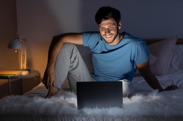 ノートパソコンでお気に入りの映画を見ている男