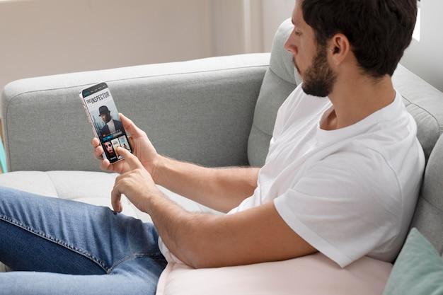 スマートフォンでお気に入りの映画を見ている男