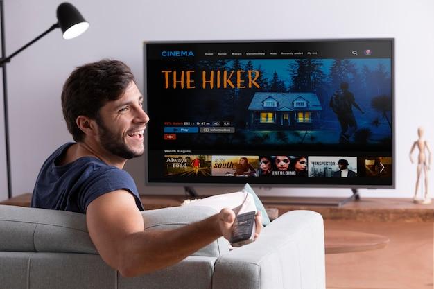 Мужчина смотрит свой любимый фильм по телевизору