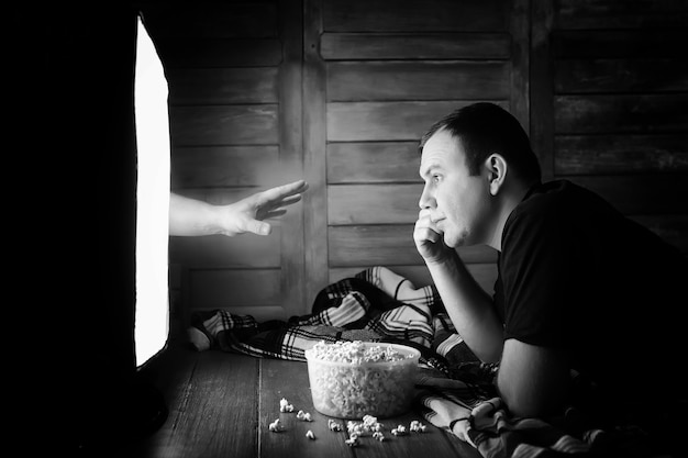 A man watching a horror movie on tv black and white