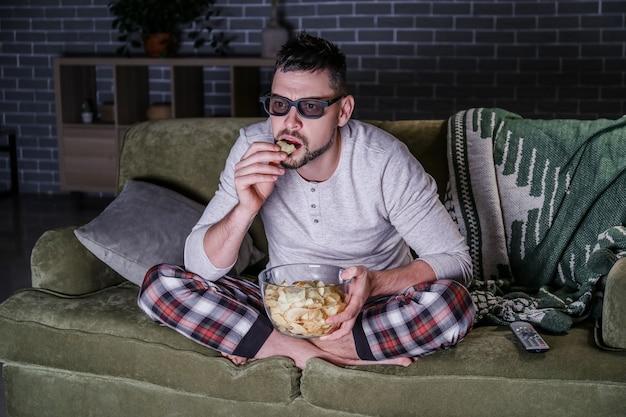 家で夜遅くに映画を見ている男