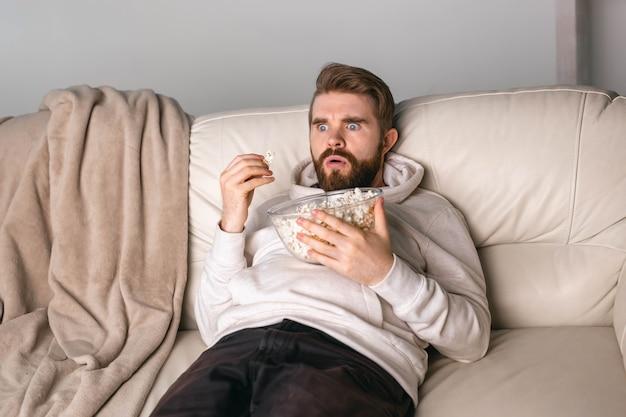 집에서 소파에 누워 영화를 보는 남자