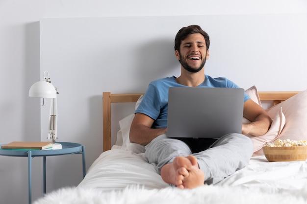 彼のラップトップでnetflixを見ている男