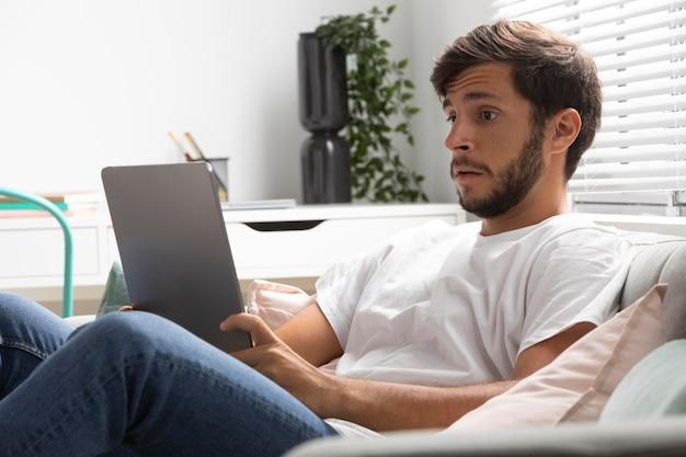 タブレットでnetflixを見ている男