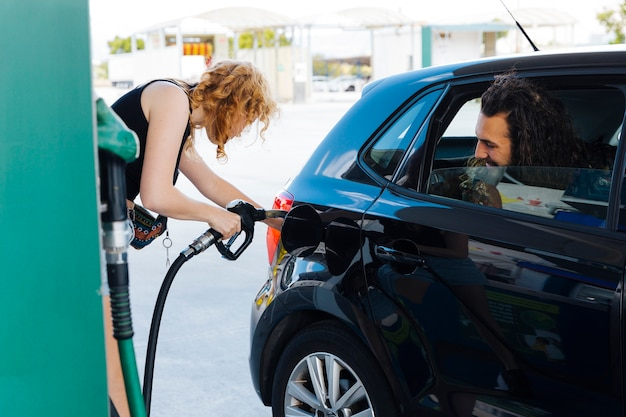 Man watching out of car window how woman filling up car