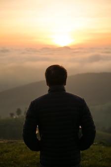 언덕에서 혼자 일출을보고하는 남자