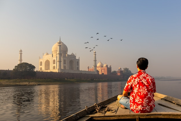Man watching sunset over taj mahal from a wooden boat with bird flying over.